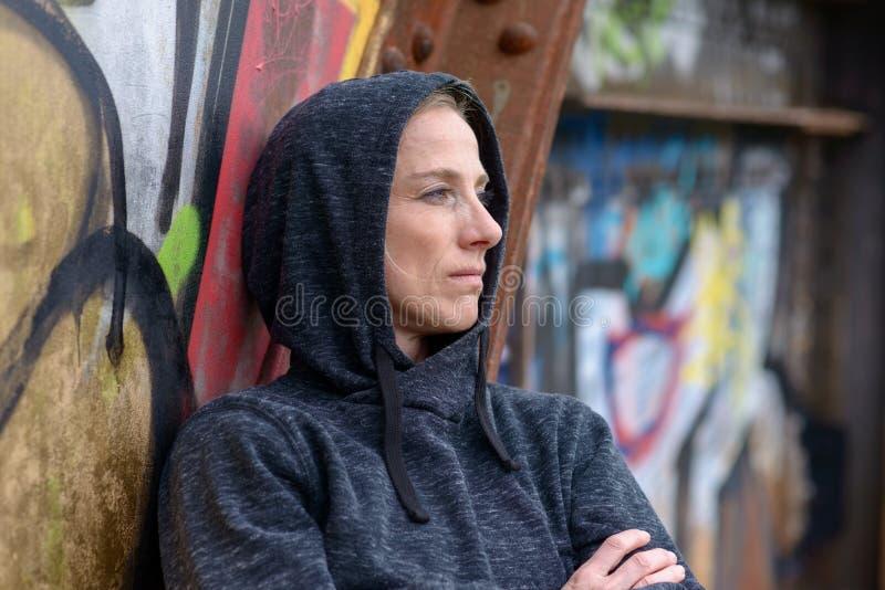 Mujer en una sudadera con capucha que se inclina contra pintada imagen de archivo libre de regalías