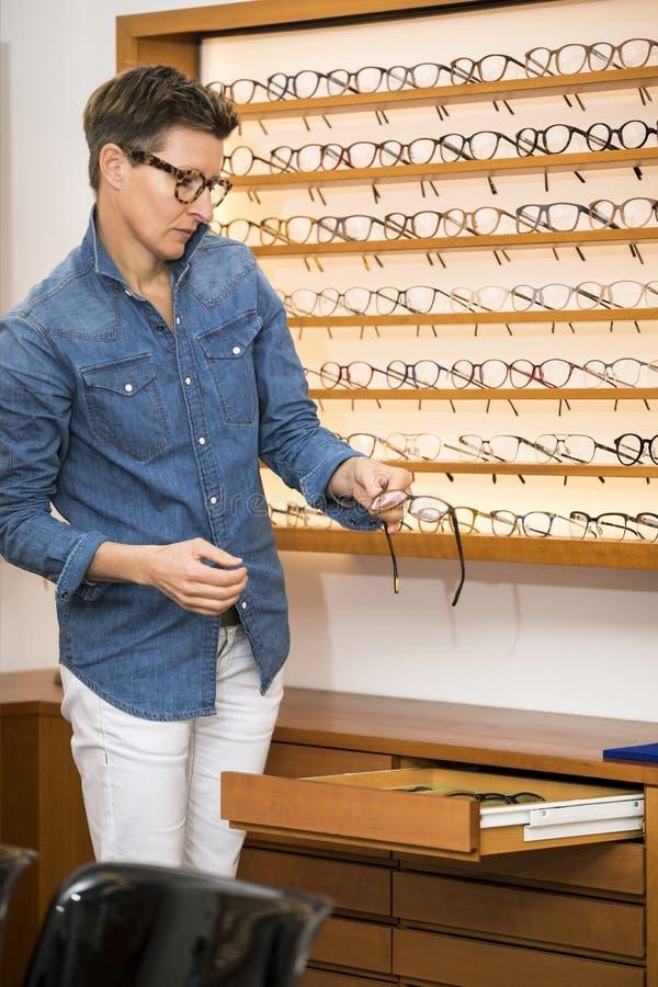 Mujer en una tienda de las gafas foto de archivo