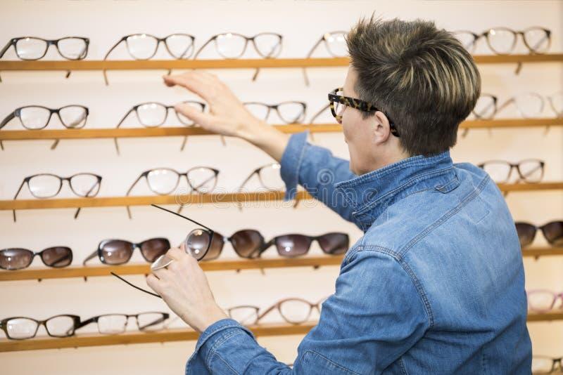 Mujer en una tienda de las gafas imágenes de archivo libres de regalías