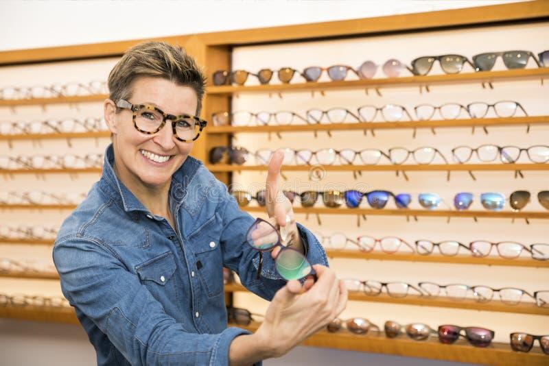 Mujer en una tienda de las gafas fotografía de archivo libre de regalías