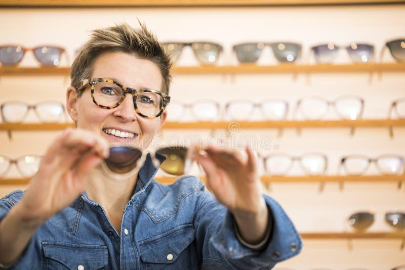 Mujer en una tienda de las gafas fotos de archivo