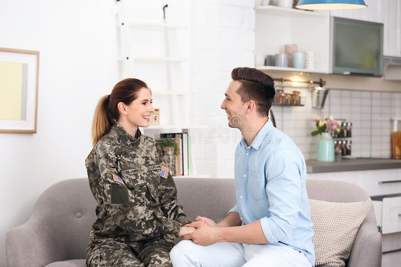 Mujer en uniforme militar con el marido en el sofá en casa fotografía de archivo