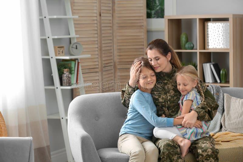 Mujer en uniforme militar con sus niños en el sofá imágenes de archivo libres de regalías