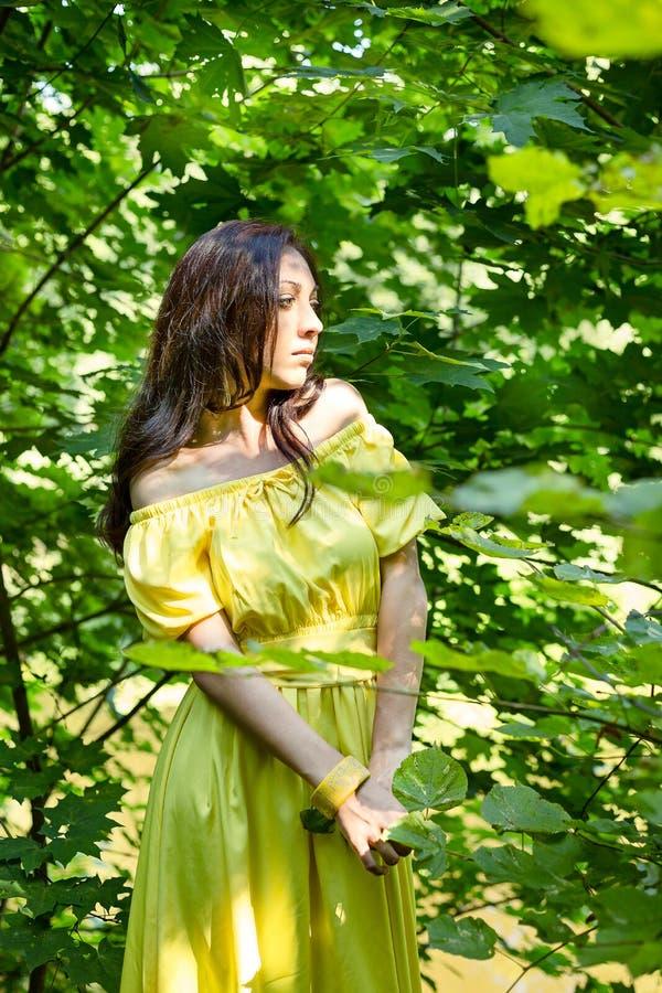 Mujer en vestido amarillo en el bosque el concepto de expectativa foto de archivo