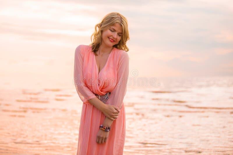 Mujer en vestido bonito en la playa durante puesta del sol fotos de archivo