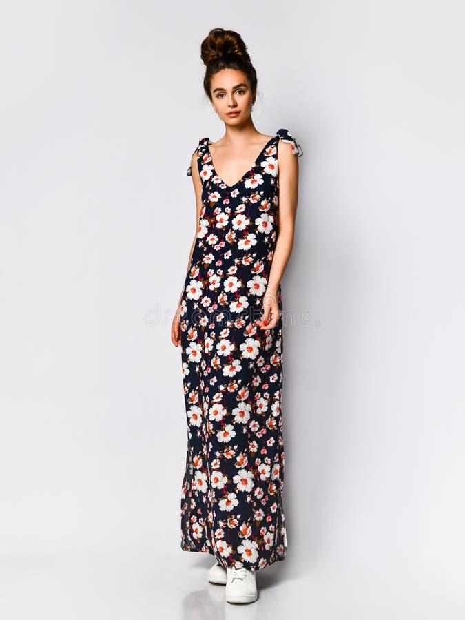 Mujer en vestido de flores largo en la tienda de la moda - retrato de la muchacha en una tienda de ropa en un vestido maxi del ve fotos de archivo libres de regalías