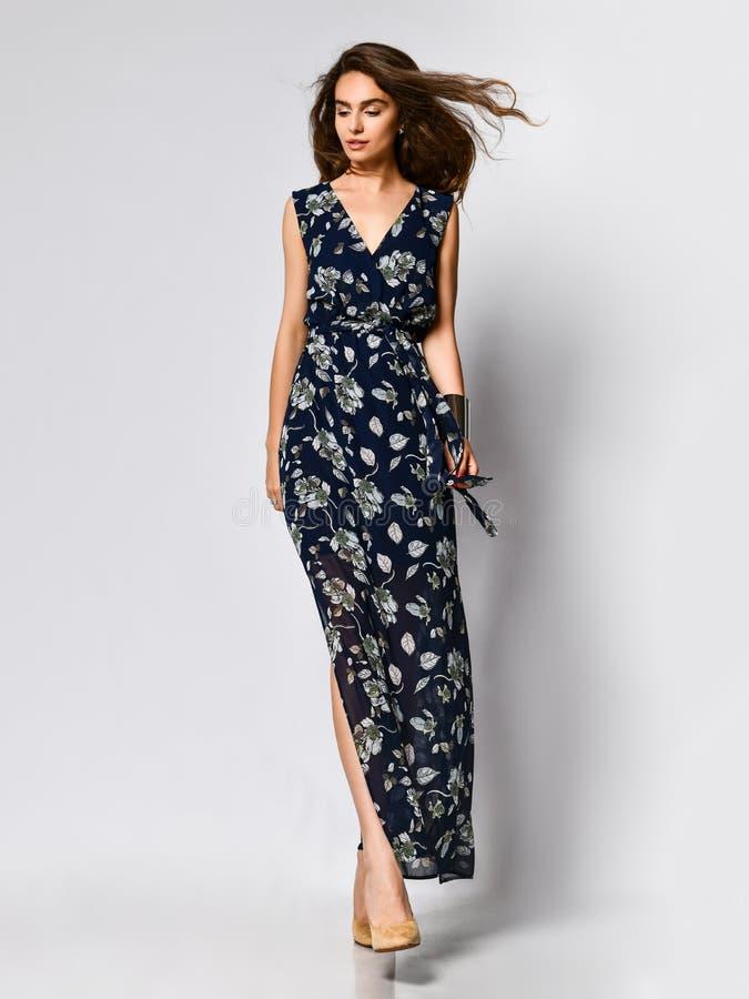 Mujer en vestido de flores largo en la tienda de la moda - retrato de la muchacha en una tienda de ropa en un vestido maxi del ve fotografía de archivo libre de regalías