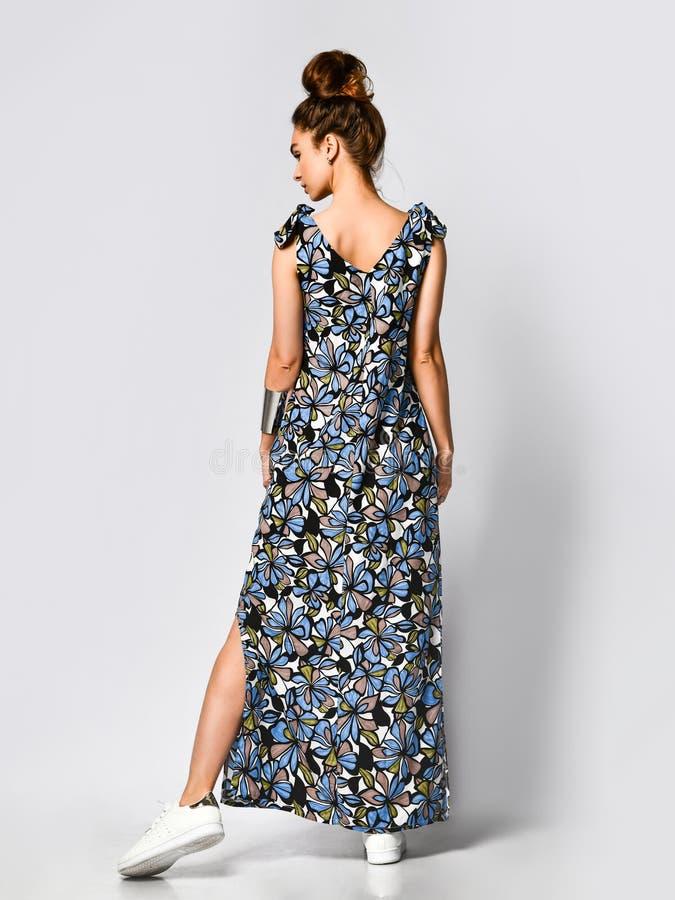Mujer en vestido de flores largo en la tienda de la moda - retrato de la muchacha en una tienda de ropa en un vestido maxi del ve foto de archivo