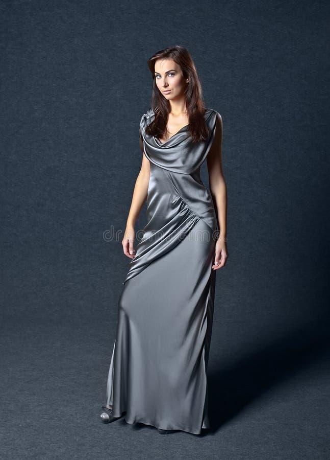 Mujer en vestido de noche gris imagenes de archivo