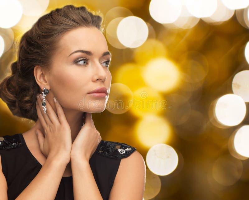 Mujer en vestido de noche y pendiente imagen de archivo