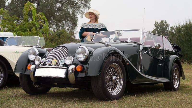 Mujer en vestido del vintage y coche de deportes clásico de Morgan fotografía de archivo