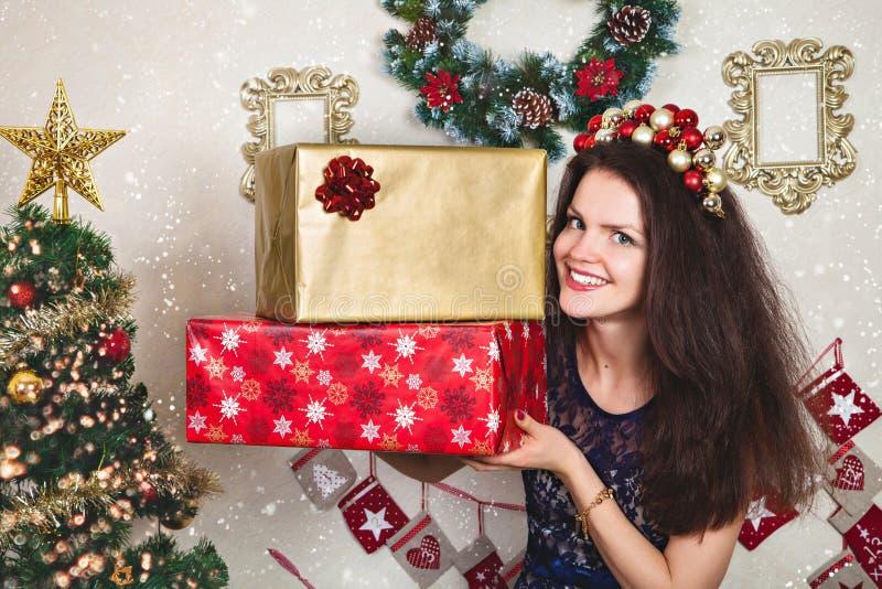 Mujer en vestido festivo del cordón con los regalos de la Navidad fotografía de archivo