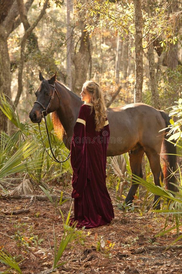 Mujer en vestido medieval con el caballo en bosque foto de archivo