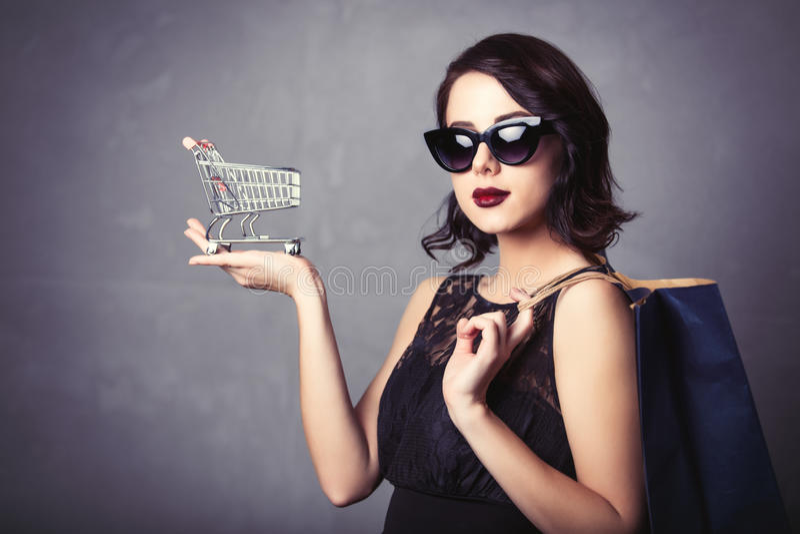 Mujer en vestido negro con el carro de la compra y el bolso imagenes de archivo