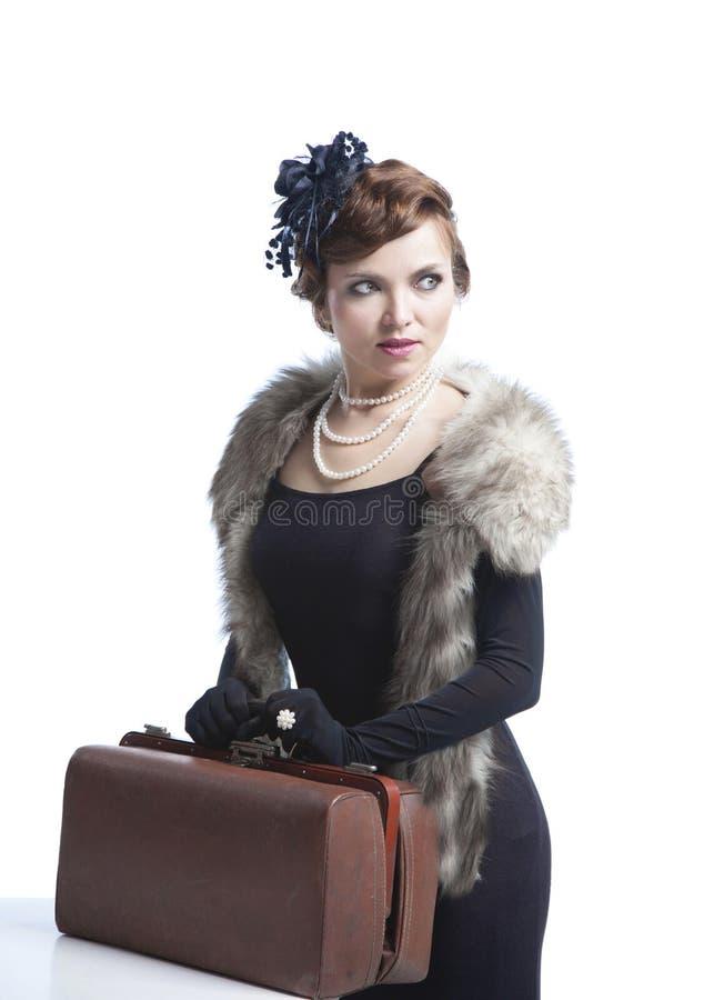 Mujer en vestido negro con la maleta fotografía de archivo libre de regalías