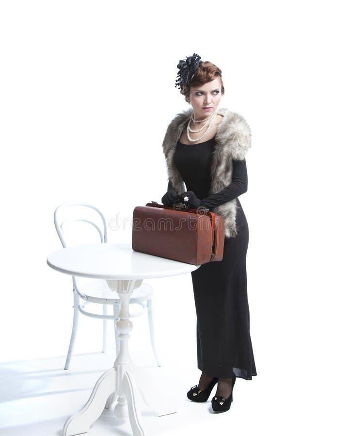 Mujer en vestido negro con la maleta fotos de archivo