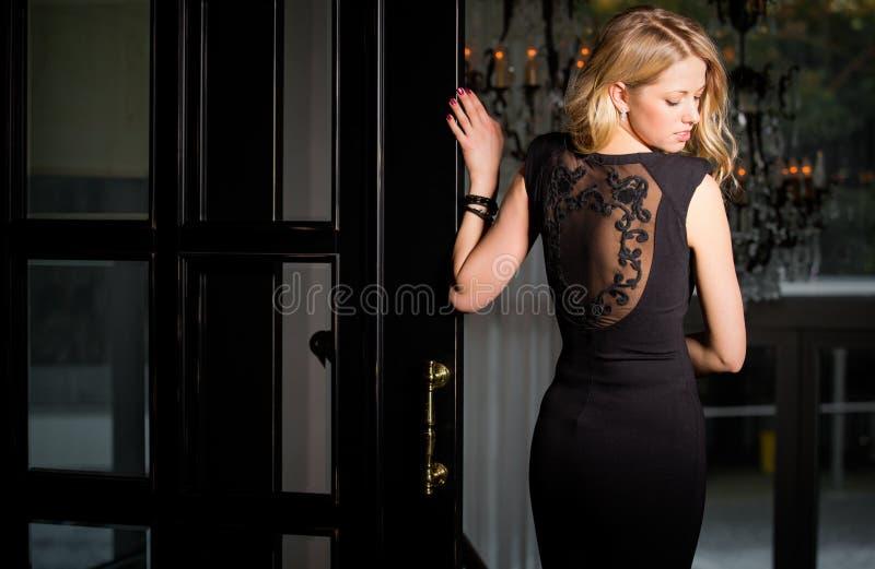 Mujer en vestido negro con la mirada trasera del cordón sobre hombro imagen de archivo