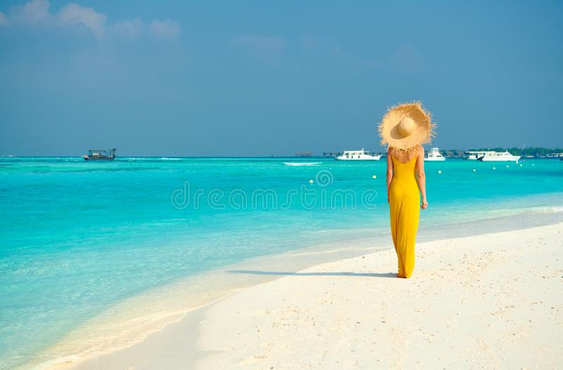 Mujer en vestido que camina en la playa tropical imagenes de archivo