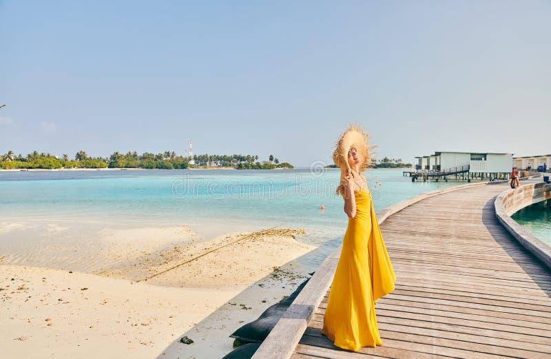 Mujer en vestido que camina en paseo mar?timo tropical de la playa imagen de archivo