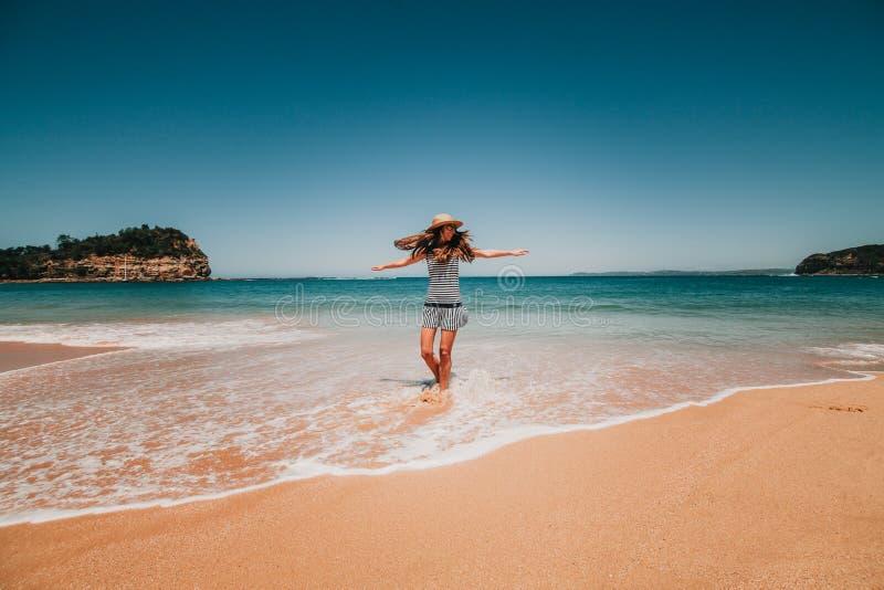 Mujer en vestido que goza de la playa en Australia fotos de archivo