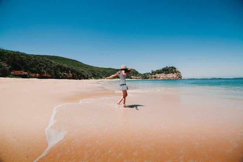 Mujer en vestido que goza de la playa en Australia fotografía de archivo
