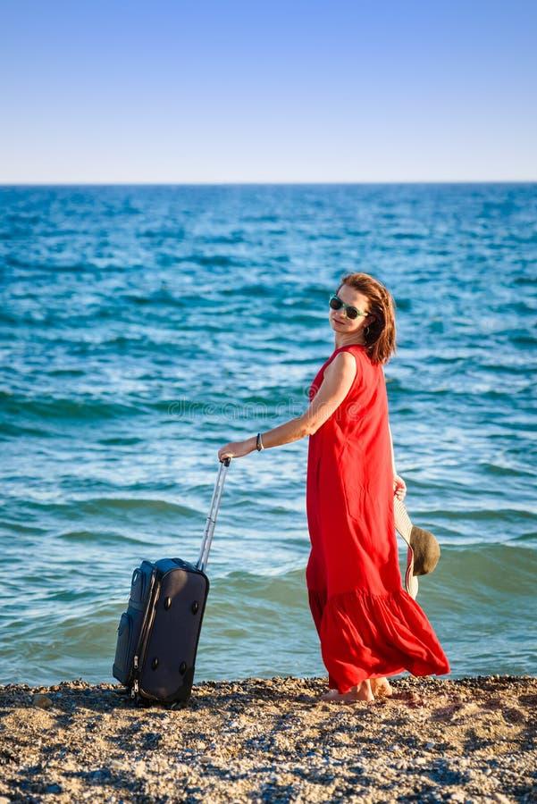 Mujer en vestido rojo con el mar de la maleta imagen de archivo