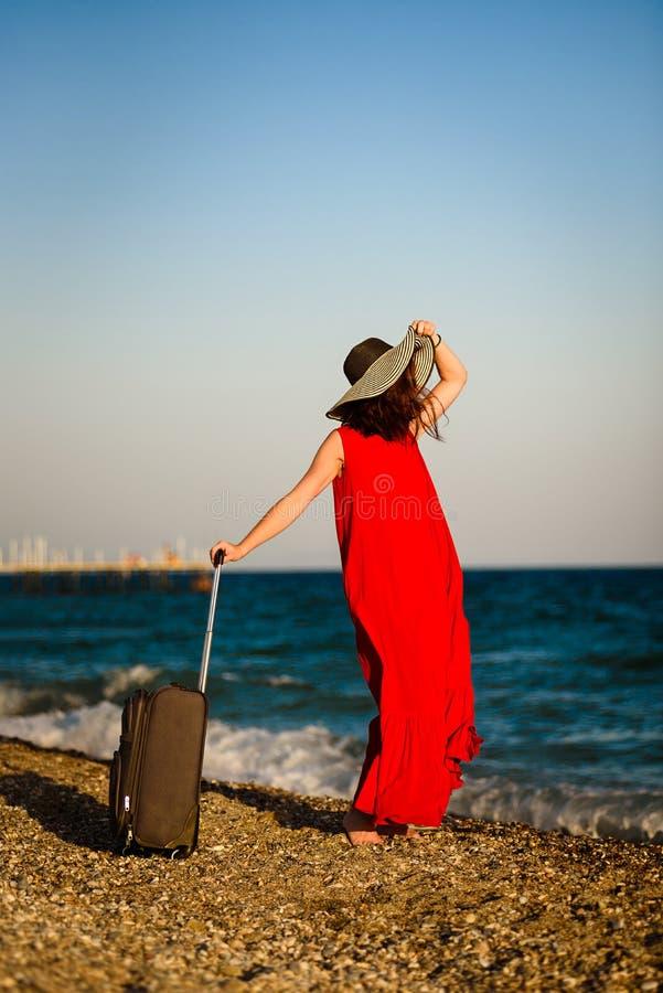 Mujer en vestido rojo con el mar de la maleta foto de archivo