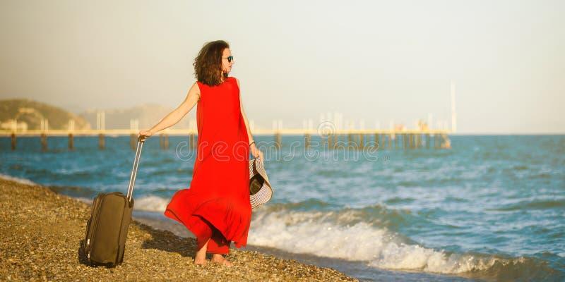 Mujer en vestido rojo con el mar de la maleta fotos de archivo