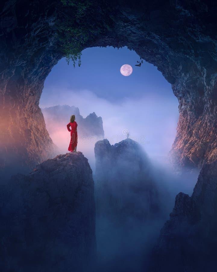 Mujer en vestido rojo contra la luna en cueva fantasmag?rica fotos de archivo libres de regalías