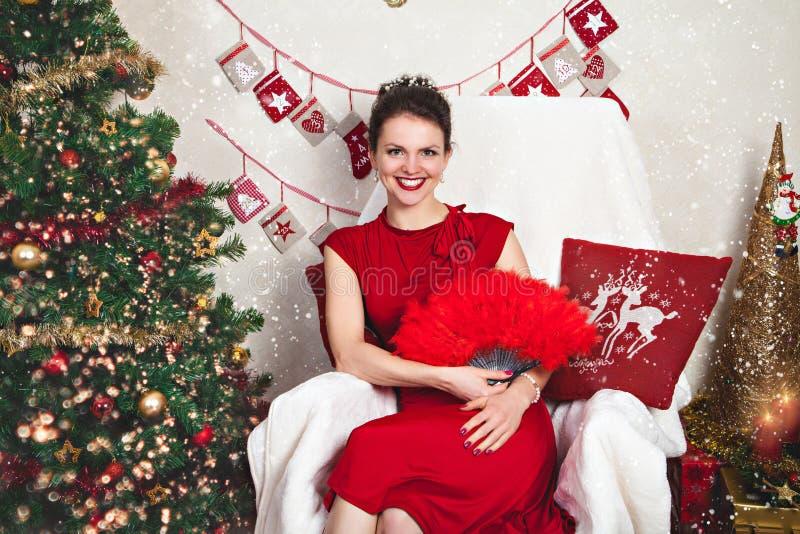 Mujer en vestido rojo festivo entre la decoración de la Navidad fotografía de archivo
