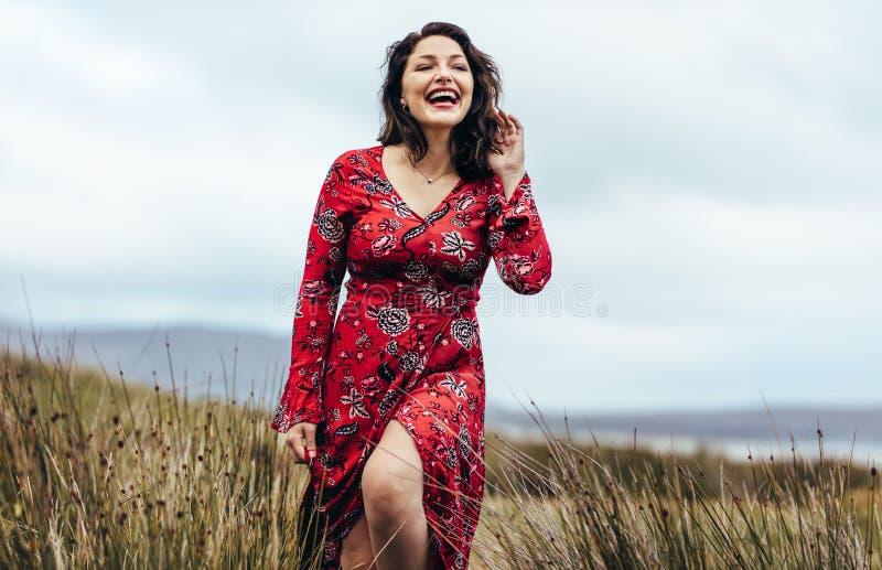 Mujer en vestido rojo hermoso que explora el campo fotografía de archivo