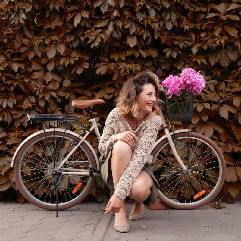 Mujer en vestido y bici imagen de archivo