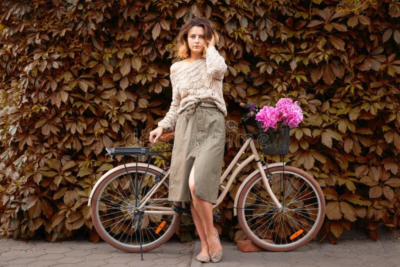 Mujer en vestido y bici foto de archivo libre de regalías