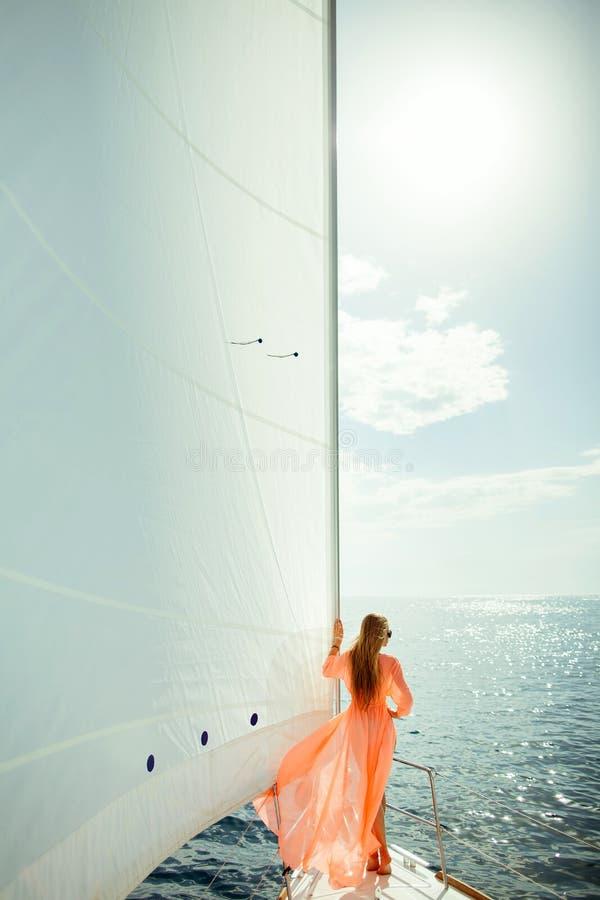 Mujer en viaje de lujo de las velas blancas de los sarong que navega foto de archivo
