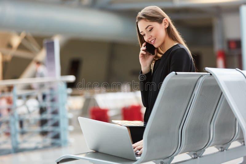 Mujer en viaje de negocios con el ordenador portátil y el smartphone foto de archivo