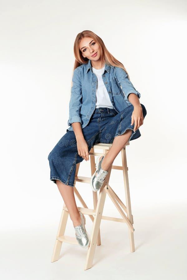 Mujer en zapatos elegantes en escalera contra blanco foto de archivo libre de regalías