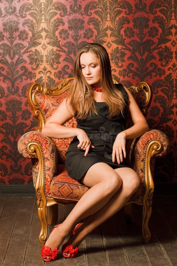 Mujer en zapatos rojos y la alineada que se sientan en silla imagen de archivo libre de regalías