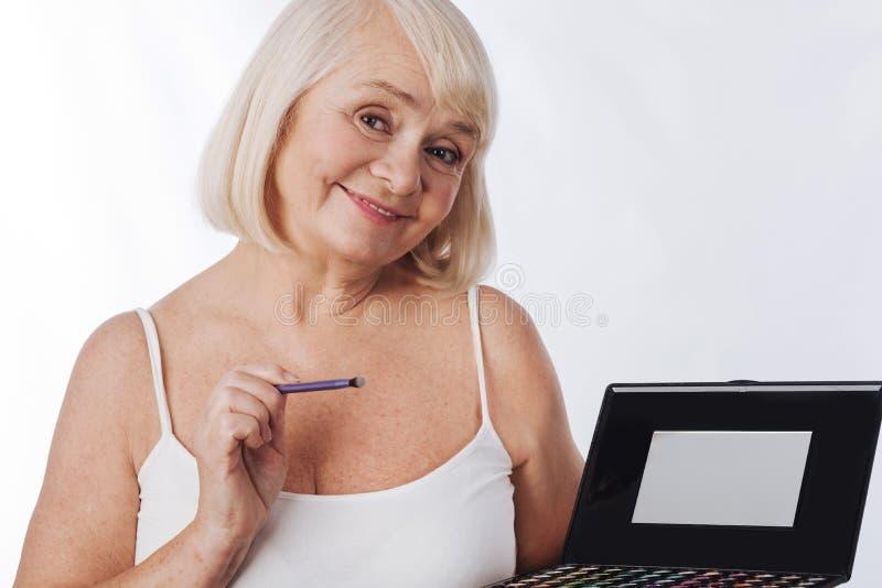 Mujer encantada agradable que aplica el sombreador de ojos fotos de archivo libres de regalías