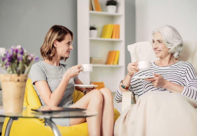 Mujer encantada alegre y su té de consumición de la abuela fotografía de archivo