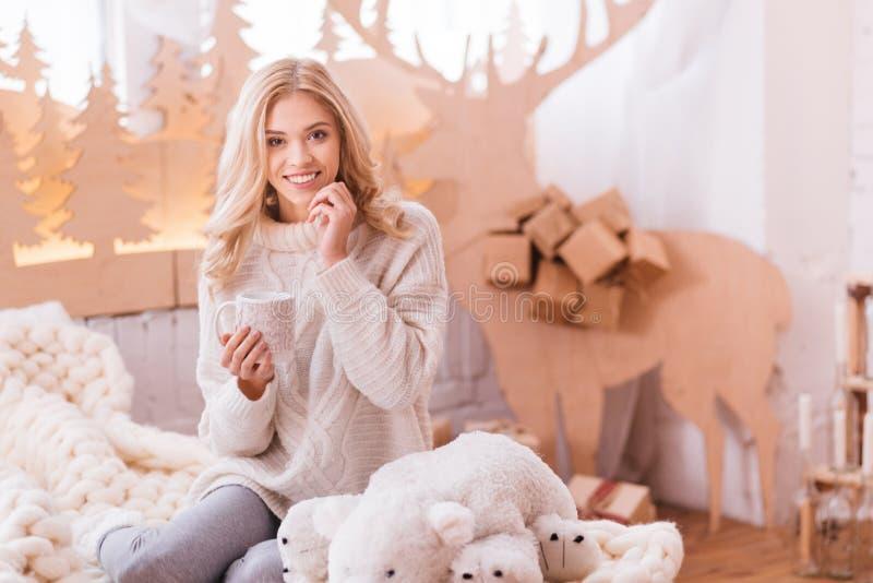 Mujer encantada apuesta que se sienta en la cama fotografía de archivo libre de regalías