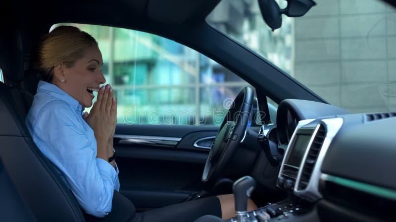 Mujer encantada con el coche comprado, interior que se sienta sinceramente sonriente, alegría ingenua imagen de archivo