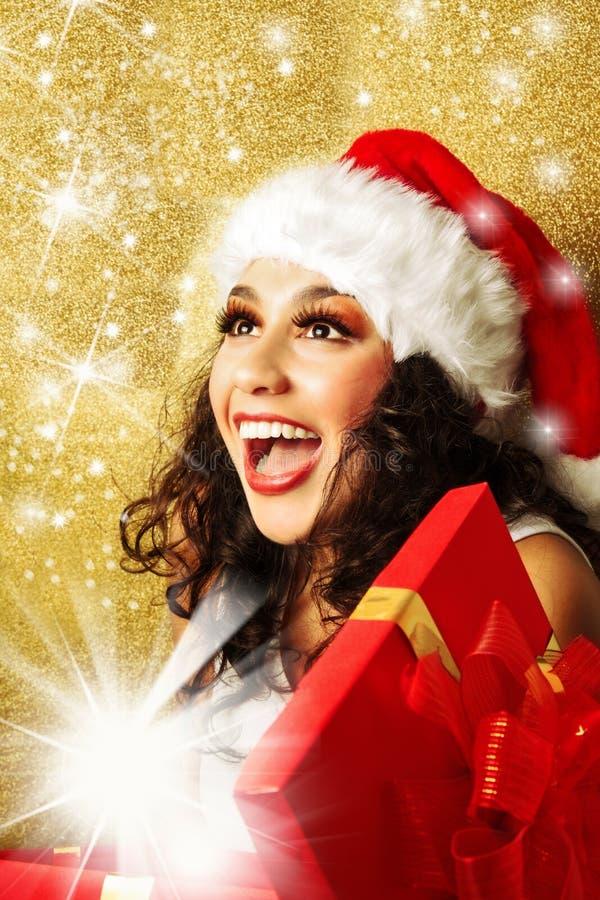 Mujer encantada con el regalo en el sombrero de Papá Noel imagen de archivo libre de regalías