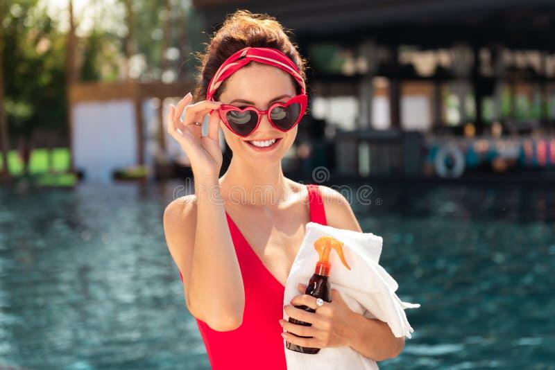 Mujer encantada feliz que fija sus gafas de sol elegantes fotos de archivo libres de regalías