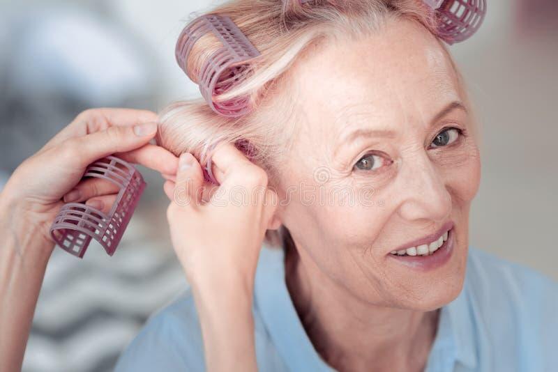 Mujer encantada feliz que usa los rodillos del pelo fotos de archivo