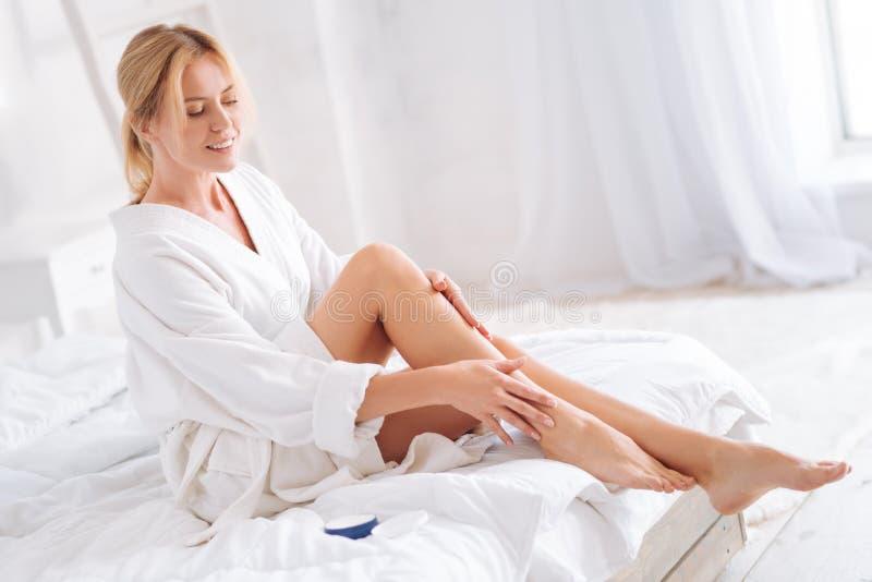 Mujer encantada que da masajes a sus piernas foto de archivo libre de regalías