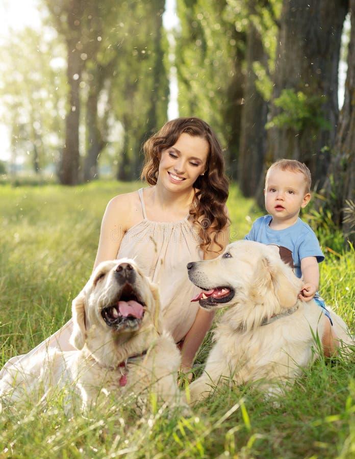 Mujer encantadora con el hijo y dos perros foto de archivo