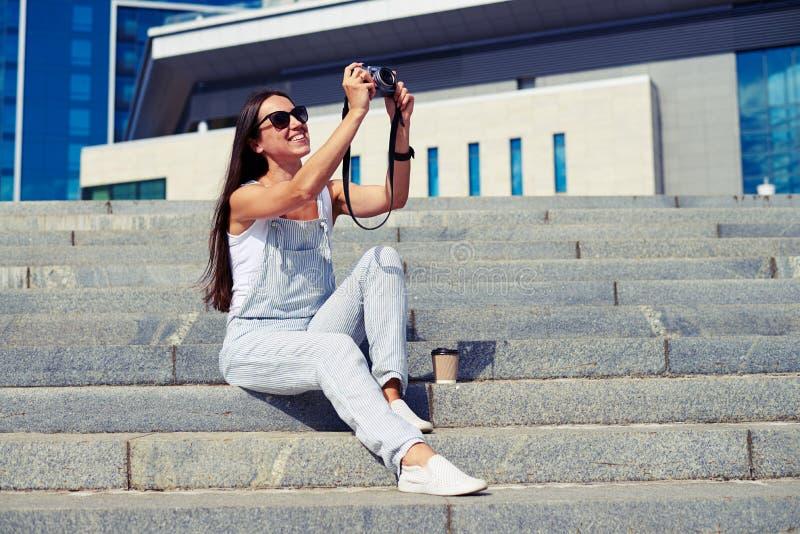 Mujer encantadora con el pelo oscuro que se sienta en las escaleras y que toma un pH imagen de archivo libre de regalías