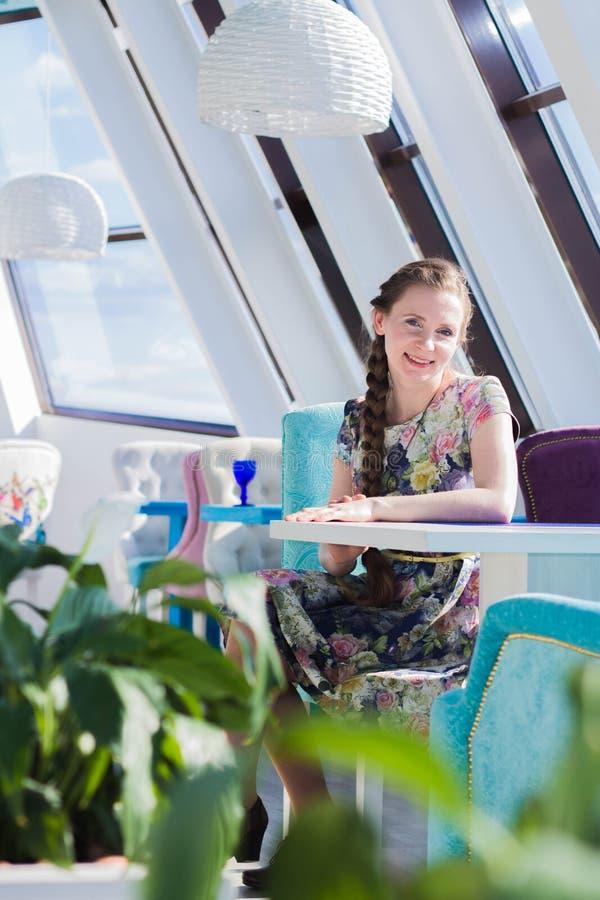 Mujer encantadora con una trenza hermosa que se sienta en un restaurante o un café fotografía de archivo libre de regalías
