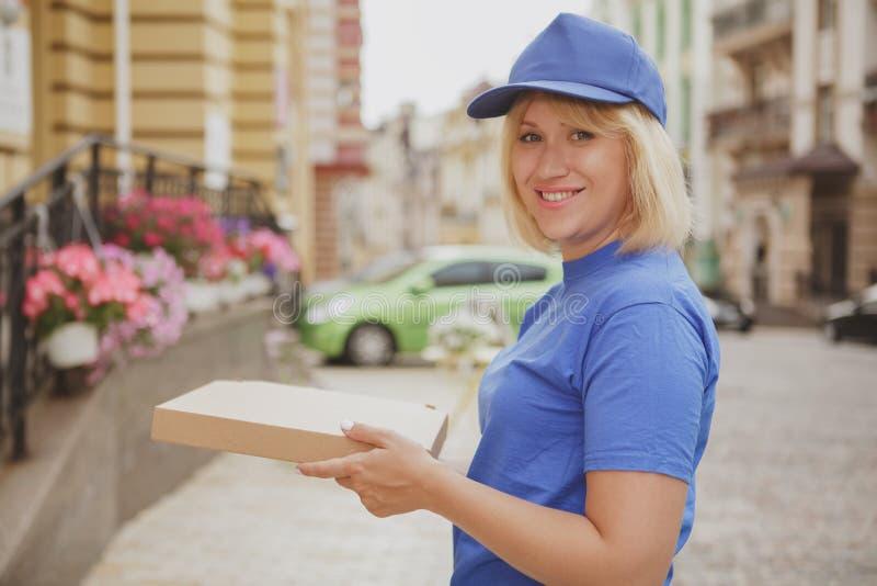 Mujer encantadora de la entrega con la caja de la pizza imagenes de archivo