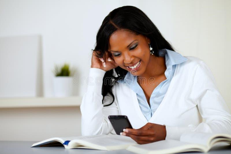 Mujer encantadora de Prettty que sonríe con el teléfono celular imagen de archivo